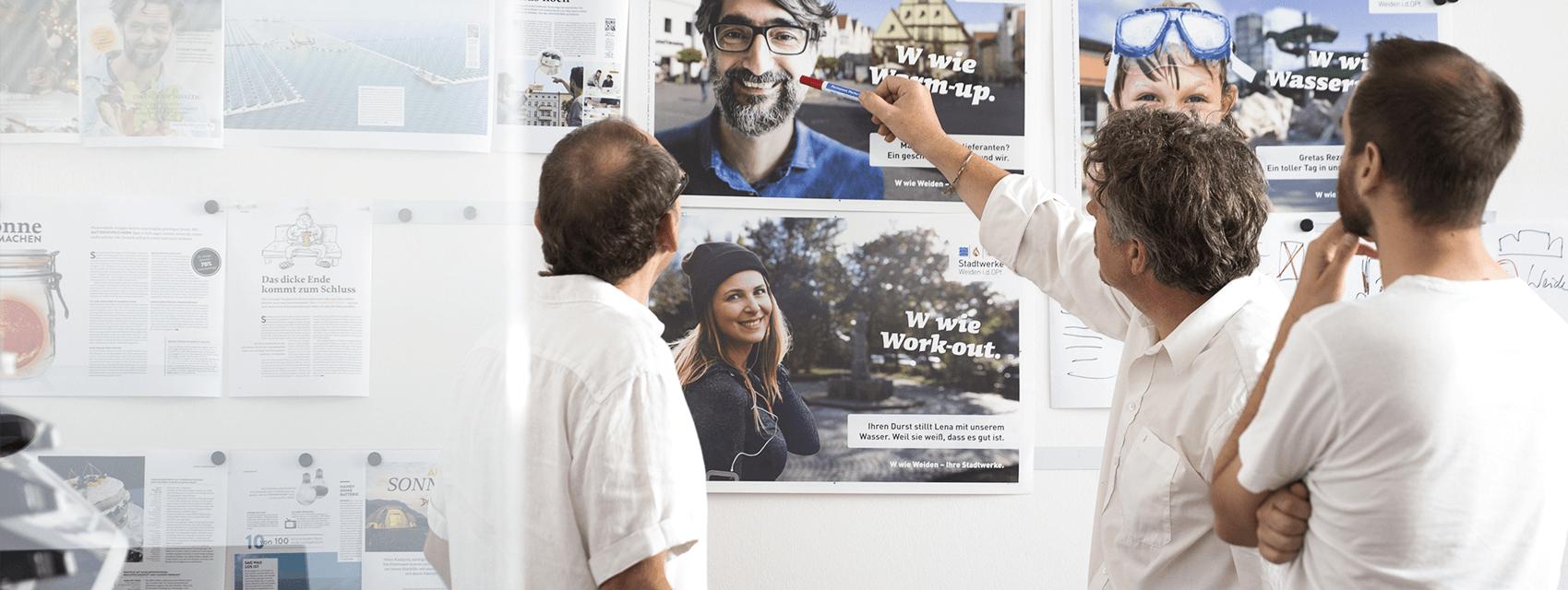Menschen schauen auf Poster - kreativer Entstehungsprozess